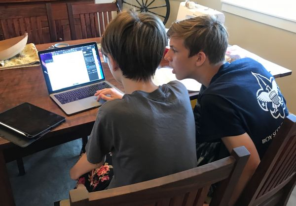 image of two high school students seated at a dining room table with a laptop computer and working collaboratively on a project
