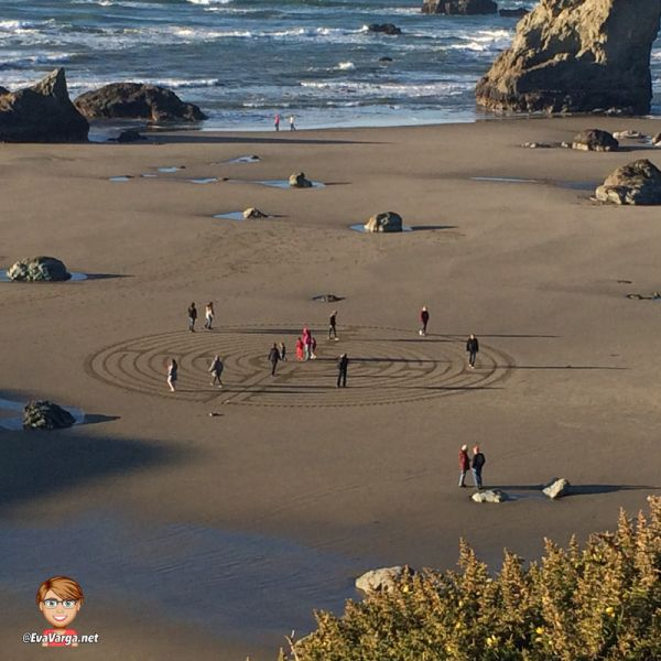 Image of people walking a hand-drawn labyrinth on a sandy beach taken from above