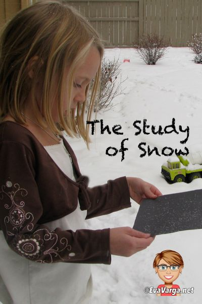 A young girl captures snow as it's falling onto black contrasting paper