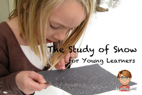 Young girl examining fresh snowflakes on a black piece of paper